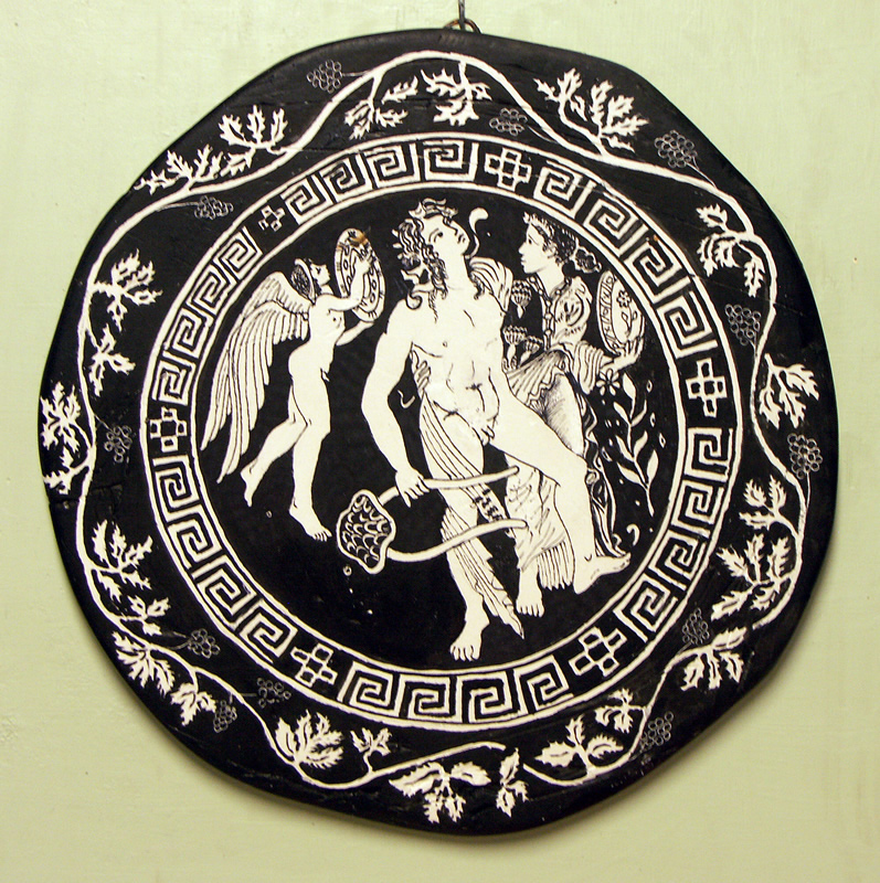 A limp Dionysus, holding a lyre, is supported by a girl with a tamborine (perhaps Ariadne) while Eros plays for them. The vine leaf around the scene would appear to settle over the level of the wine when cup is used. Early fourth century B.C. Original 24cm. Copy by Diana Webber, 2015.